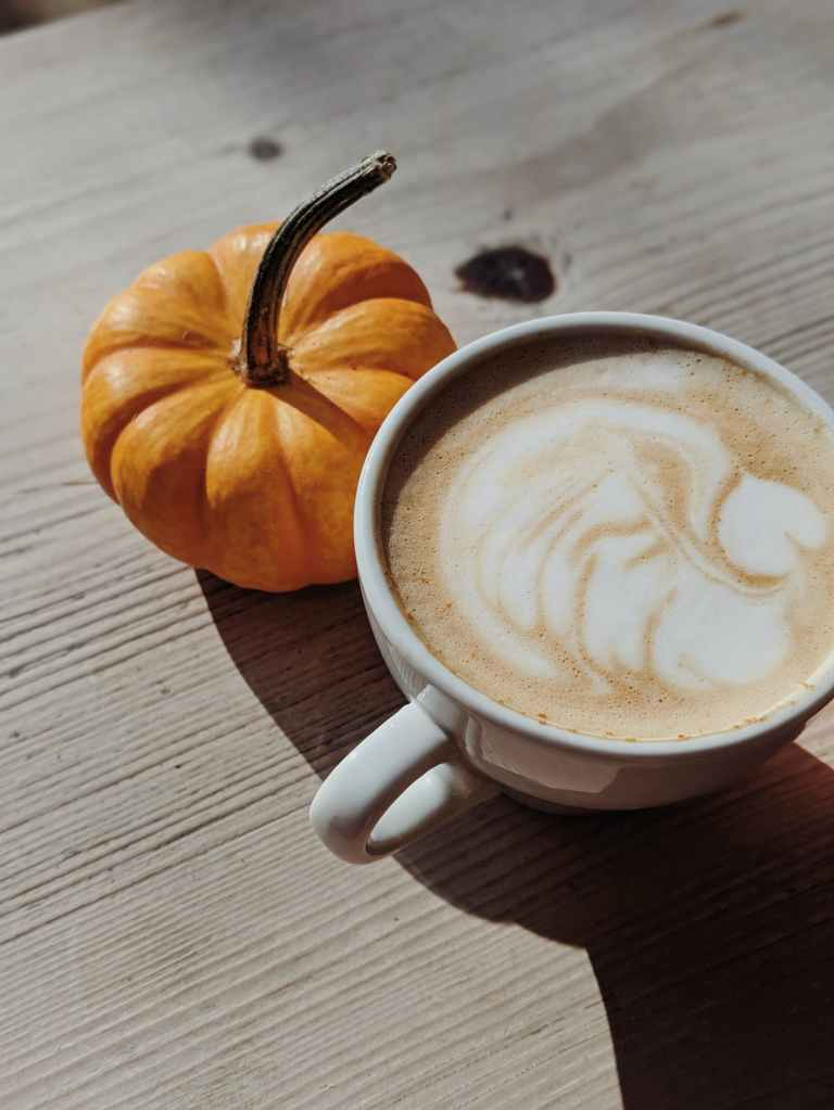 Latte in a white mug beside small orange pumpkin.