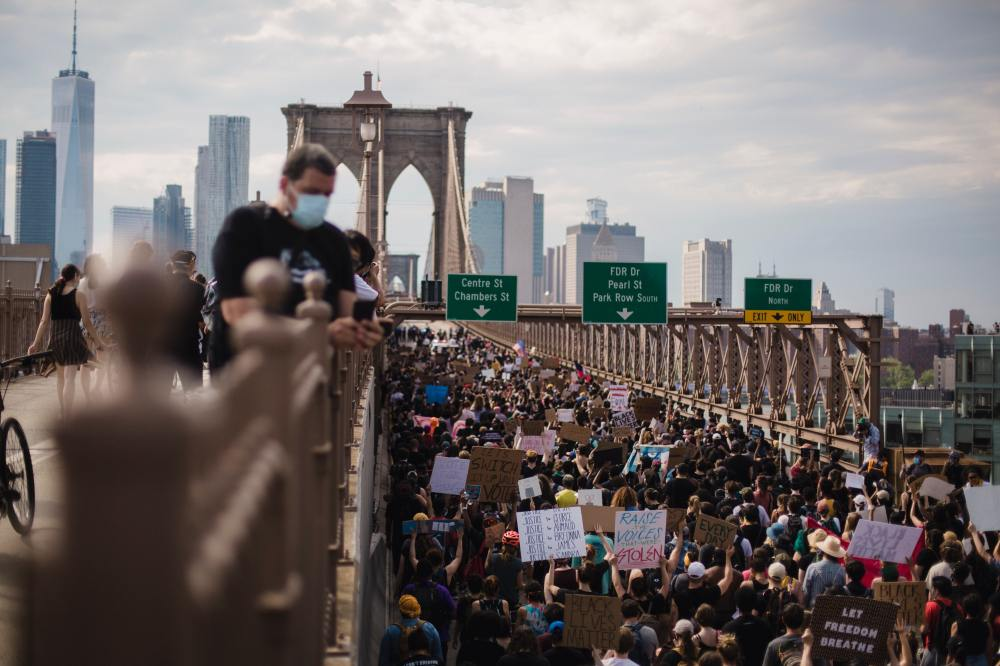 Photo of protestors marching over bridge.