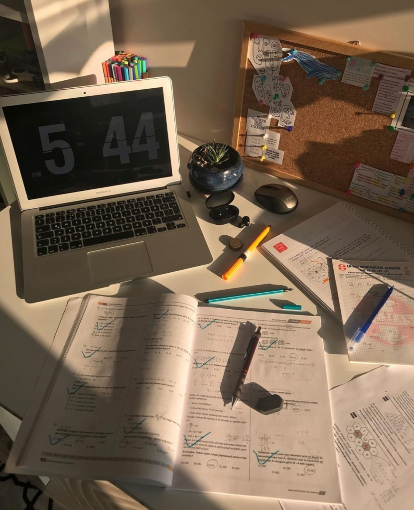 Busy desk with laptop and assignments.