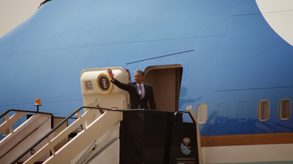 Former President Barack Obama waving in front of the entrance to Air Force One in Saudi Arabia.