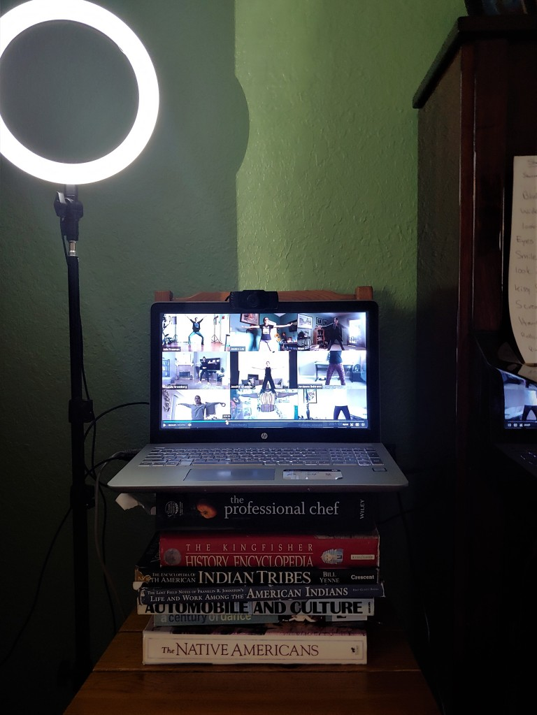 Laptop setup on top of books with ring light to side